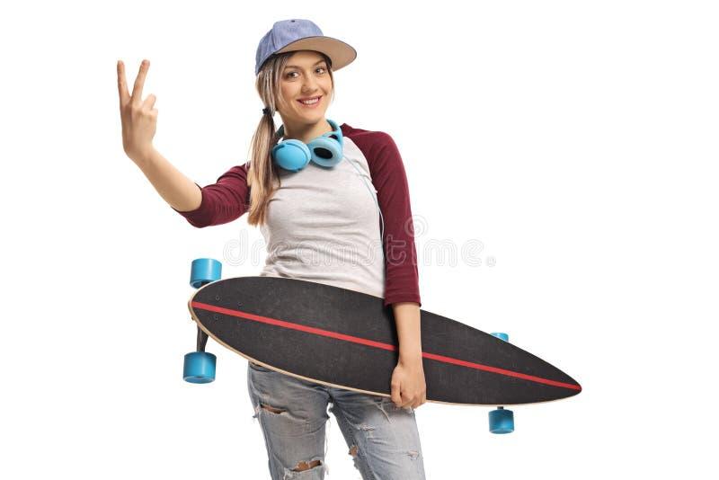 Kvinnlig skateboradåkare som rymmer en longboard och gör ett fredtecken arkivfoto
