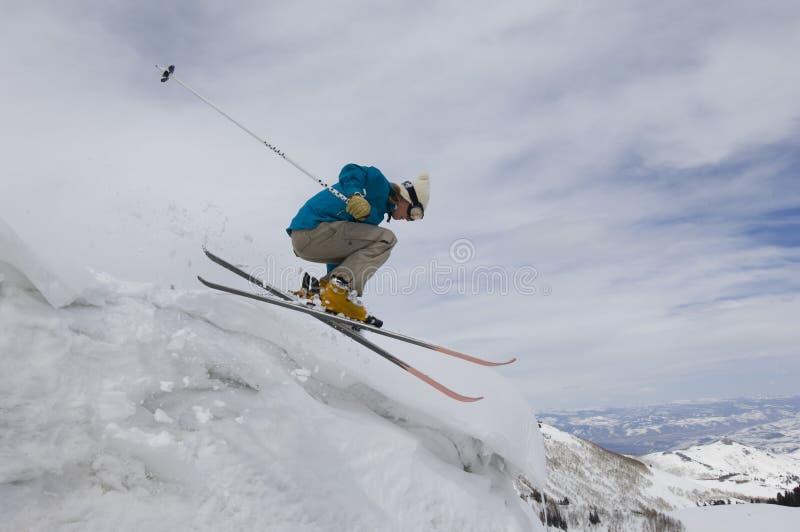 Kvinnlig skidåkare som hoppar av iskall överhäng royaltyfri bild