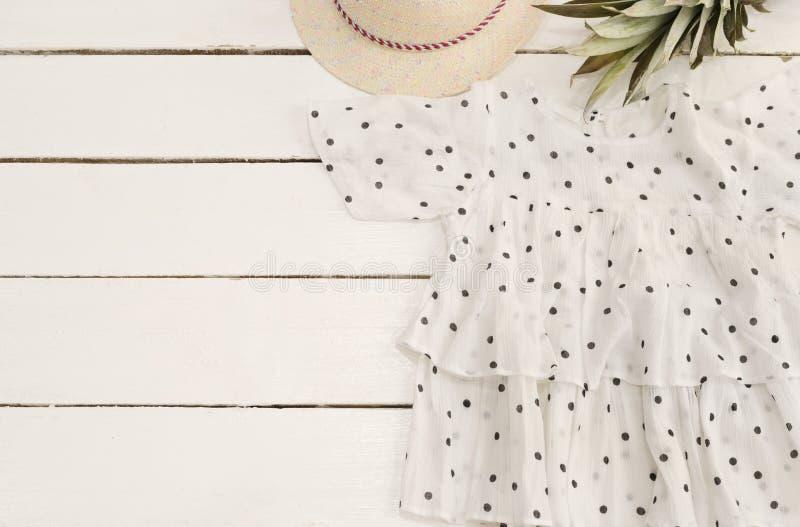 Kvinnlig skjorta, sugrörhatt, ananas, prickar Vit gammal träbakgrund royaltyfri fotografi