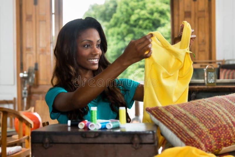 Kvinnlig skräddare för afrikansk amerikan på arbete med färgrik kläder fotografering för bildbyråer