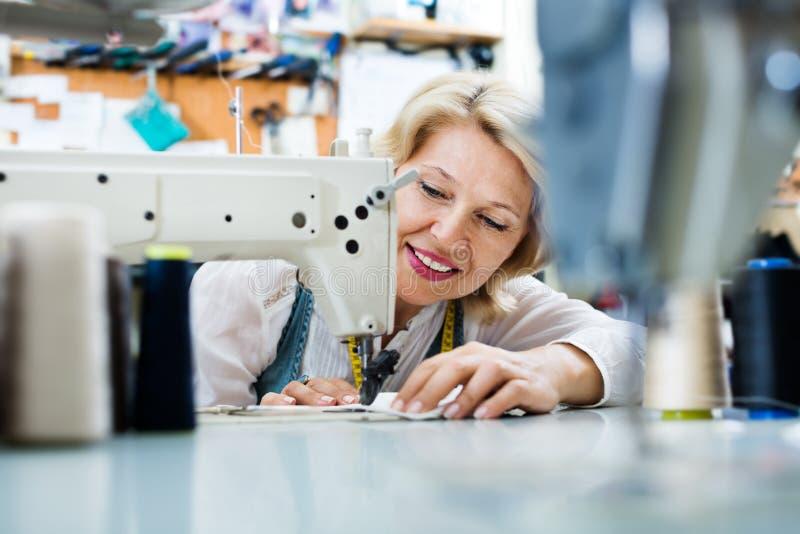 Kvinnlig skräddare som arbetar på symaskinen royaltyfria foton