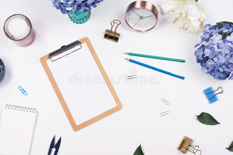 Kvinnlig skrivbordworkspaceram med skönhetordning av bukettvanliga hortensior, skrivplattan, kaffekoppen, gem, klockan, blyertspe royaltyfria foton
