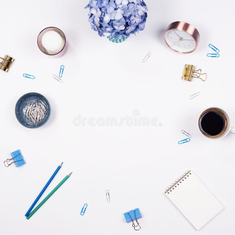Kvinnlig skrivbordworkspaceram med skönhetordning av den bukettvanliga hortensior, skrivplattan, anteckningsboken, gem, klockan,  arkivbilder