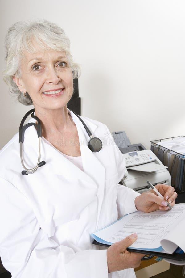 Kvinnlig skrivplatta för doktor Writing Notes On arkivfoton