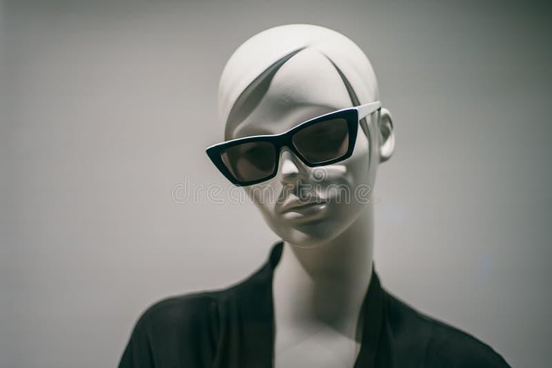 Kvinnlig skyltdocka i solglasögon i boutique Falskt huvudslut upp i modelager fotografering för bildbyråer