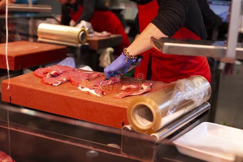 Kvinnlig slaktare i likformig med den stora kniven f?r k?tt som klipper p? den ber?mda marknaden i Barcelona, Catalonia, Spanien  fotografering för bildbyråer