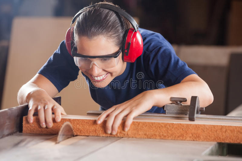 Kvinnlig snickare Cutting Wood With Tablesaw arkivfoto