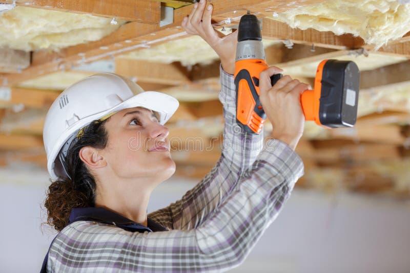 Kvinnlig snickare som använder drillborren på trästrukturen royaltyfri foto