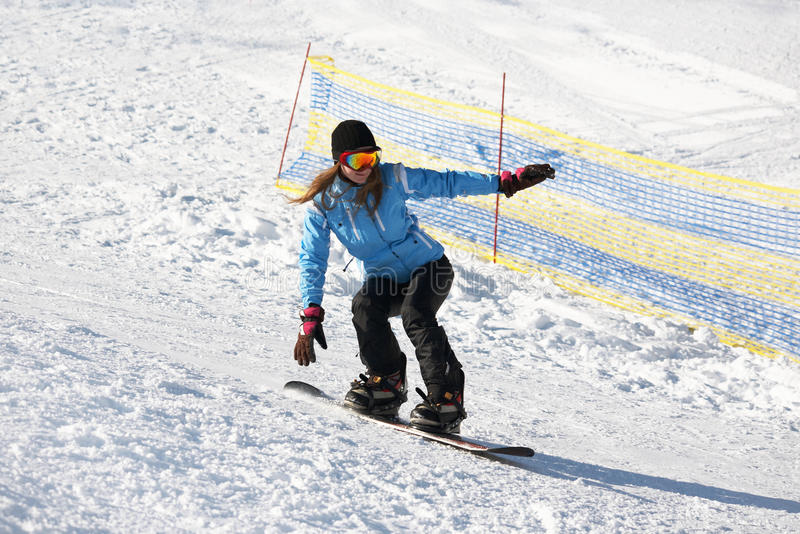 Kvinnlig Snowboarder på en snö arkivfoton