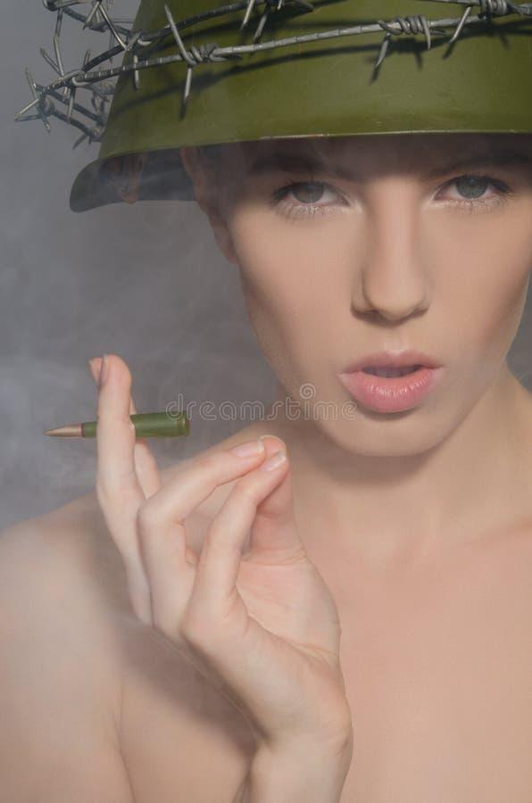 Kvinnlig soldat i hjälm med kula-cigaretten royaltyfria foton