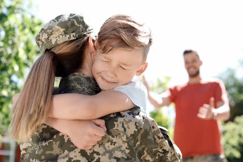 Kvinnlig soldat med hennes son utomhus Militärtjänst arkivfoton