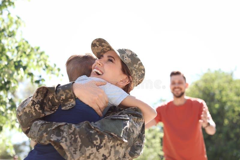 Kvinnlig soldat som kramar med hennes son, utomhus Militärtjänst arkivfoton