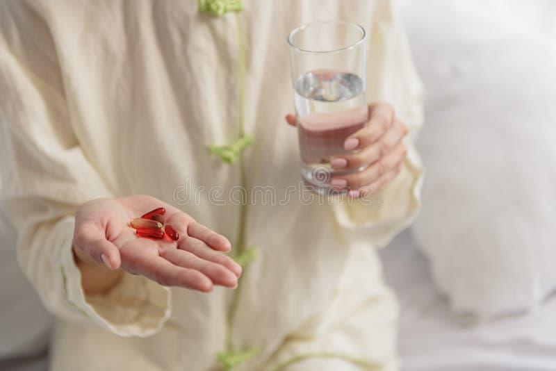 Kvinnlig som äter vitaminer och dricksvatten arkivfoton