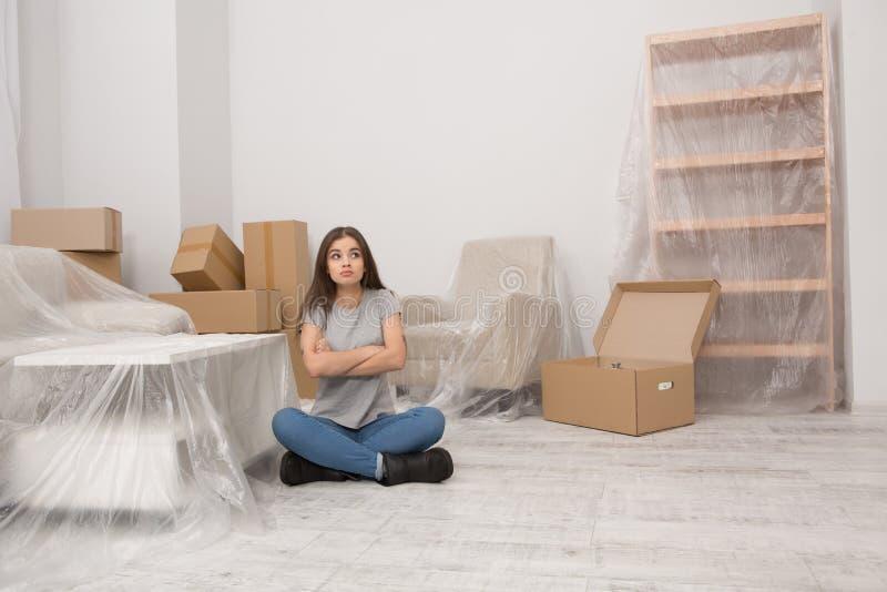 Kvinnlig som försöker att vara lugna medan ny lägenhet för inflyttning royaltyfri bild
