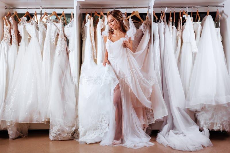 Kvinnlig som försöker på bröllopsklänningen arkivfoton