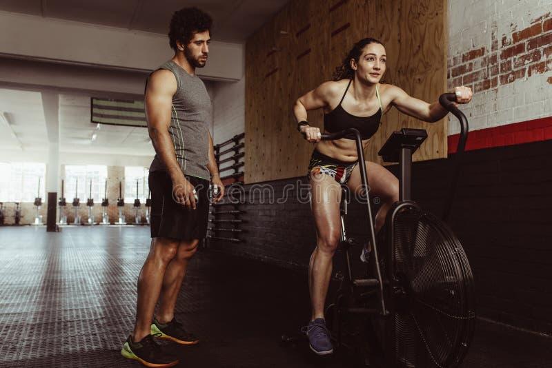 Kvinnlig som gör cardio genomkörare på idrottshallen med instruktören fotografering för bildbyråer