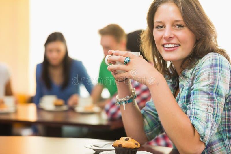 Kvinnlig som har kaffe och muffin på coffee shop fotografering för bildbyråer