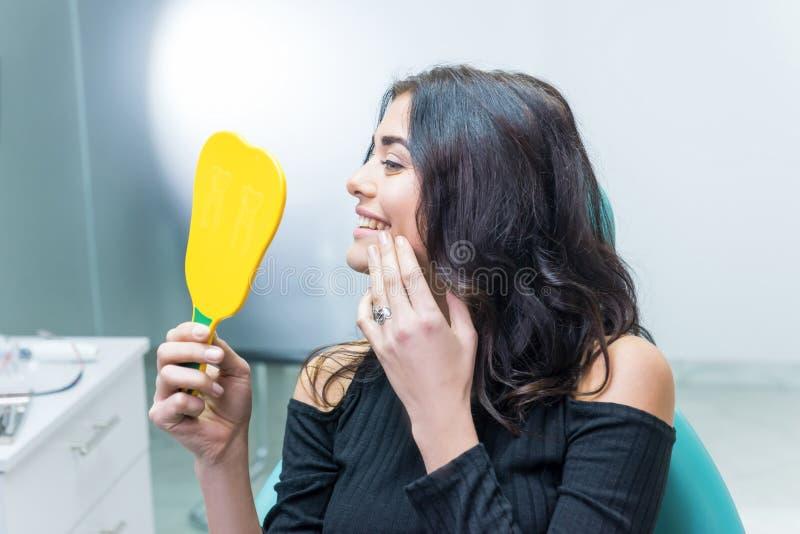 Kvinnlig som kontrollerar tänder i spegel arkivbilder