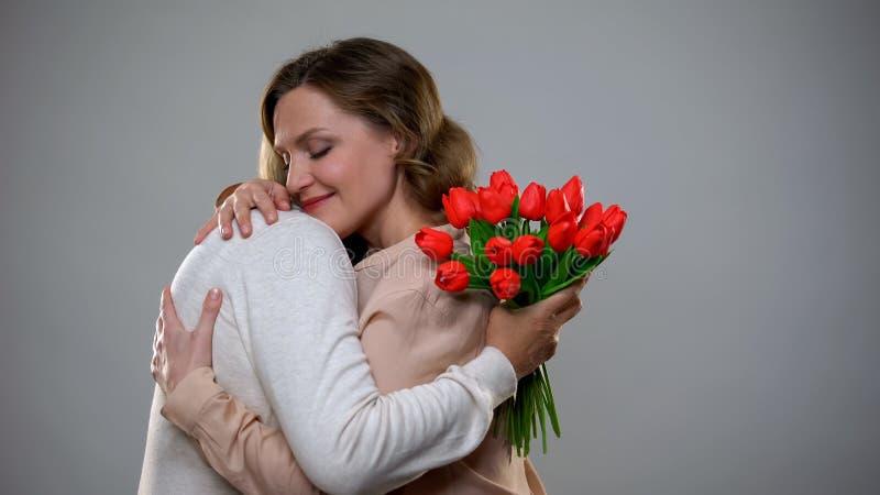 Kvinnlig som kramar, vuxen moder som rymmer tulpanbuketten, mordagberöm royaltyfri foto