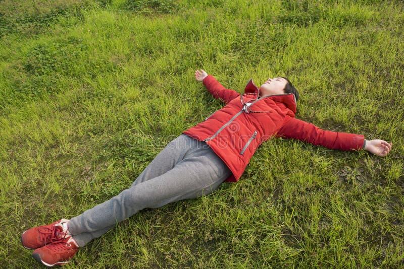 Kvinnlig som lägger på gräsmatta fotografering för bildbyråer