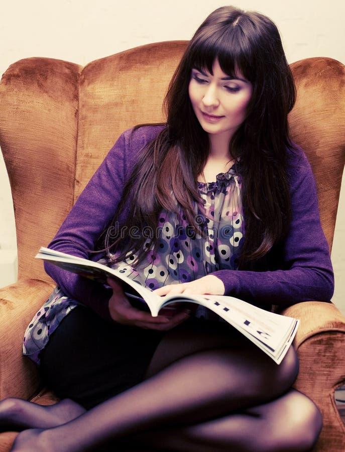 Kvinnlig som läser en tidskrift på teatid royaltyfria bilder