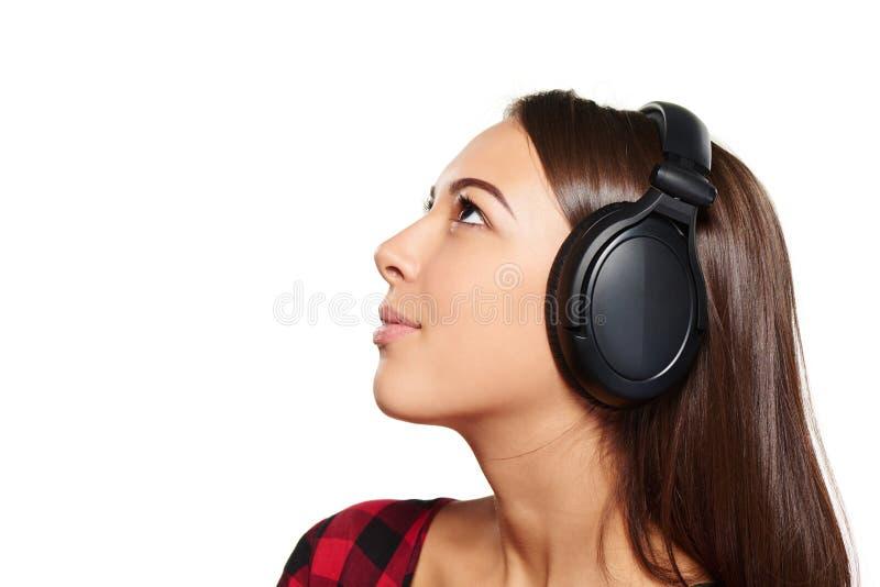 Kvinnlig som lyssnar tycka om musik i hörlurar arkivbilder