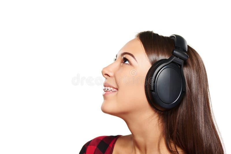 Kvinnlig som lyssnar tycka om musik i hörlurar arkivbild