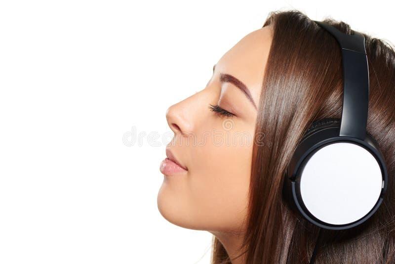 Kvinnlig som lyssnar tycka om musik i hörlurar med stängda ögon arkivfoto