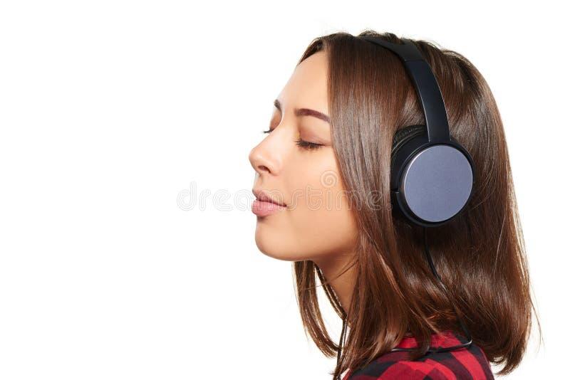 Kvinnlig som lyssnar tycka om musik i hörlurar med stängda ögon royaltyfri fotografi