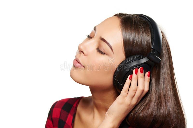 Kvinnlig som lyssnar tycka om musik i hörlurar med stängda ögon royaltyfri bild
