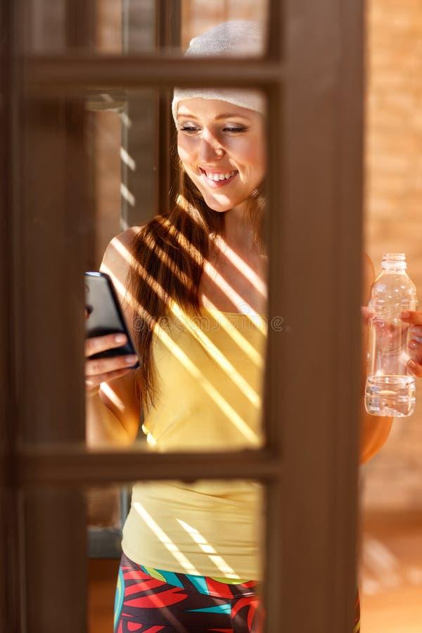 Kvinnlig som ser på mobiltelefonen vid fönstret royaltyfria bilder
