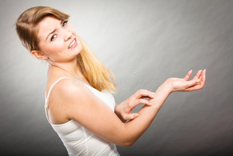 Kvinnlig som skrapar hennes kliande arm med den överilade allergin royaltyfria foton
