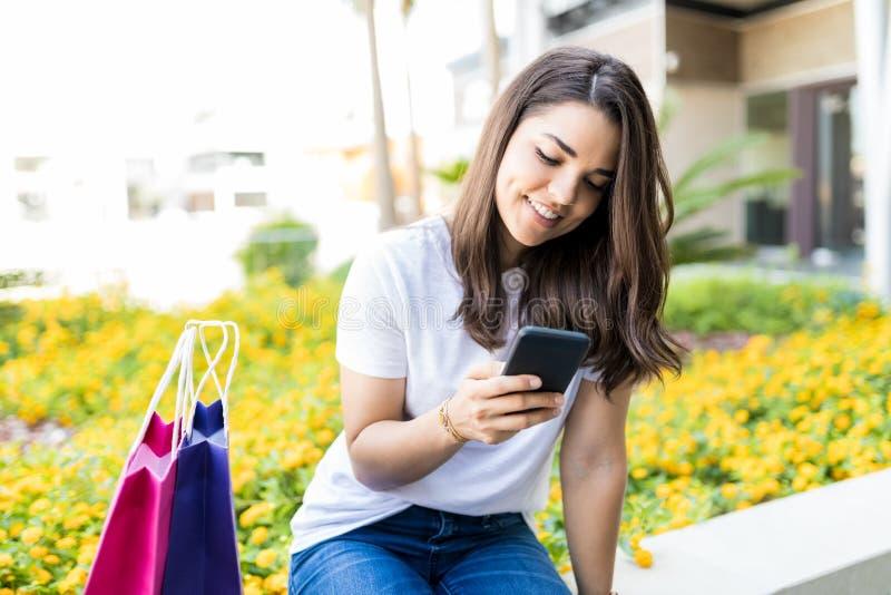 Kvinnlig som smsar på mobiltelefonen, medan sitta vid shoppingpåsar arkivbilder
