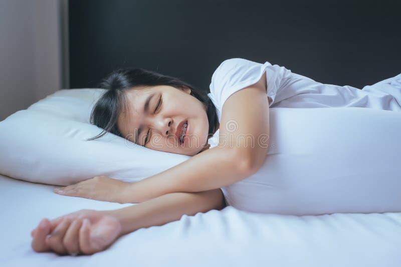 Kvinnlig som sover på sängen och de malande tänderna royaltyfria foton