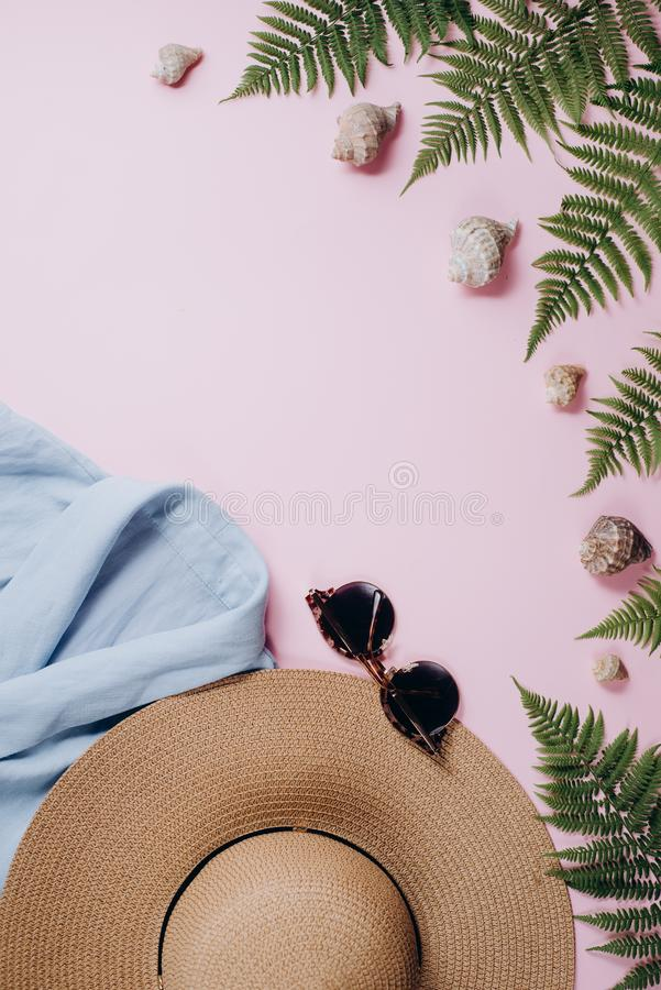 Kvinnlig sommarmodesammansättning med blusen, hatt, solglasögon, ormbunke, snäckskal på rosa bakgrund arkivbilder