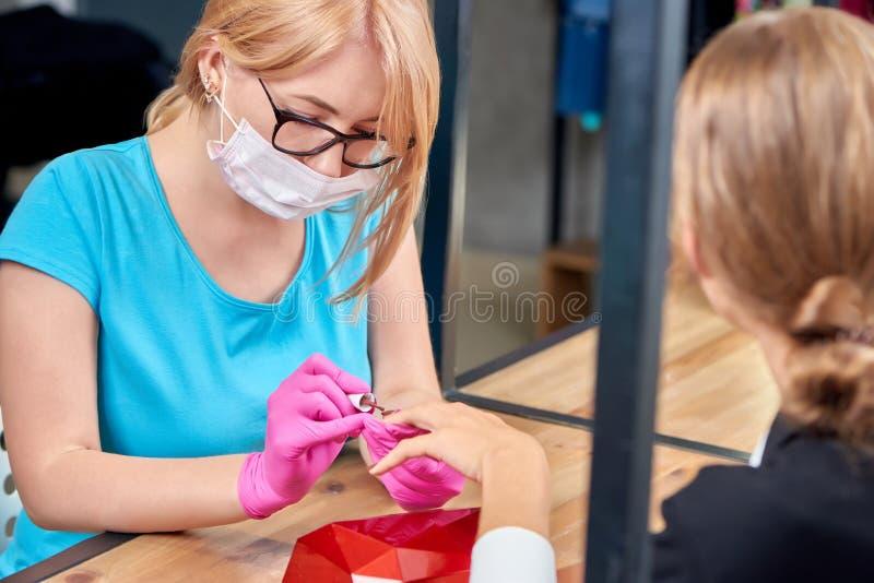 Kvinnlig specialist för skönhet i process av att göra manikyr till kvinnan i modern salong arkivfoto