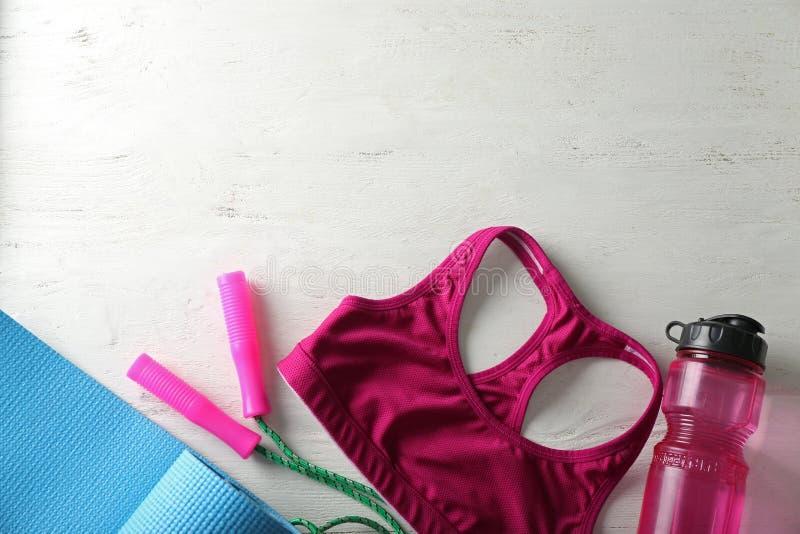 Kvinnlig sportöverkant, flaska av vatten, mattt och hoppa rep för yoga på vit träbakgrund royaltyfri foto
