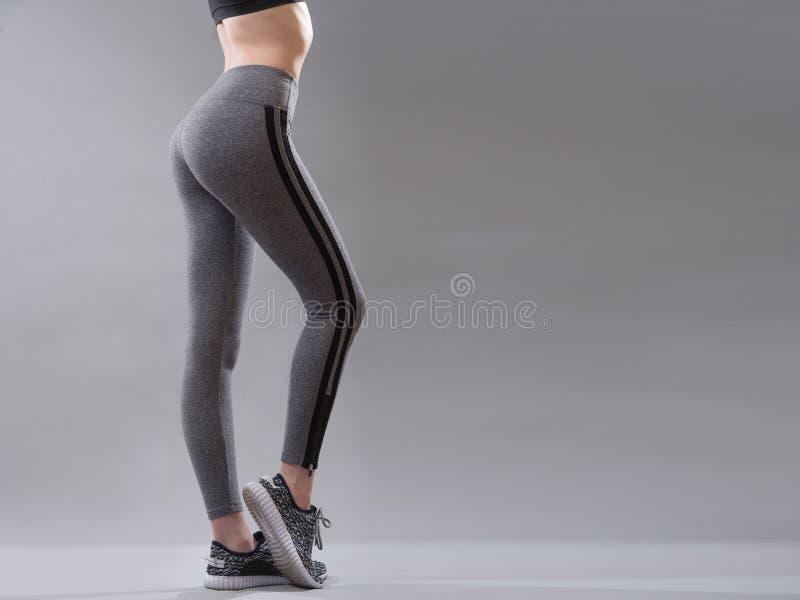 Kvinnlig sportswearkläder på perfekt kropp, gymnastikskor och gråa damaskerflåsanden arkivfoto
