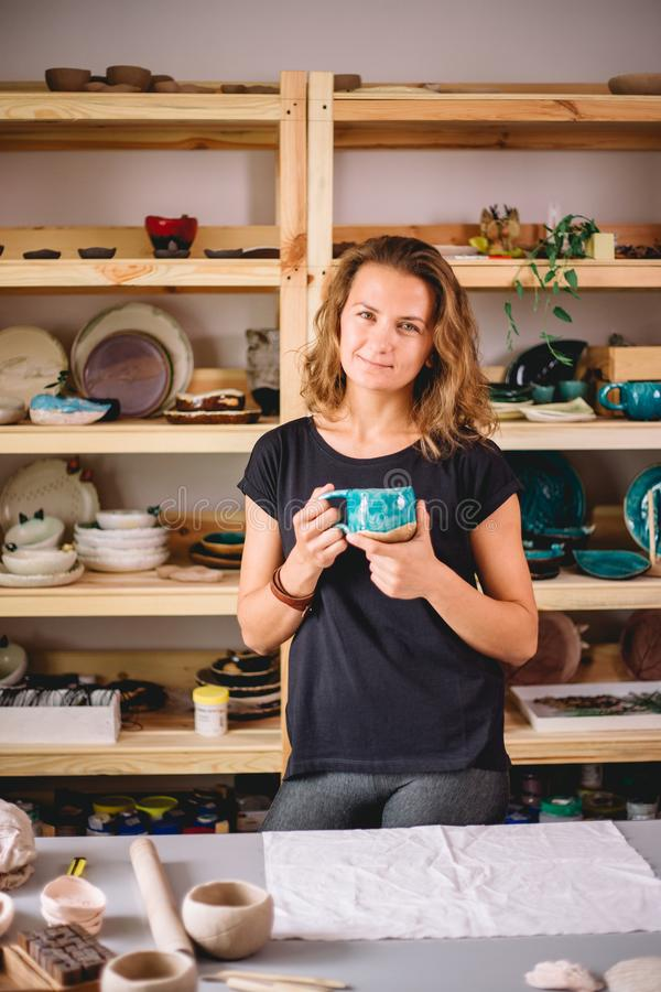 Kvinnlig ställning med färdiga redskap som ler ceramistarbetsplatsen med bakade koppar fotografering för bildbyråer