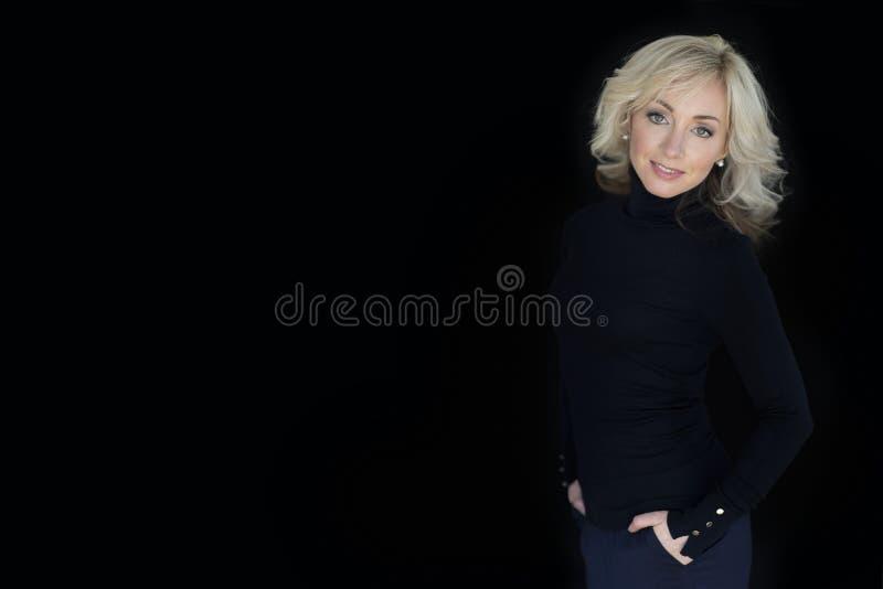 Kvinnlig stående på en svart bakgrund royaltyfri fotografi