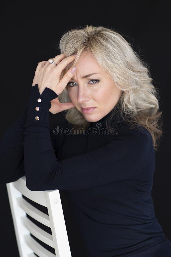 Kvinnlig stående på en svart bakgrund Kvinna blondinen, sinnesrörelser fotografering för bildbyråer
