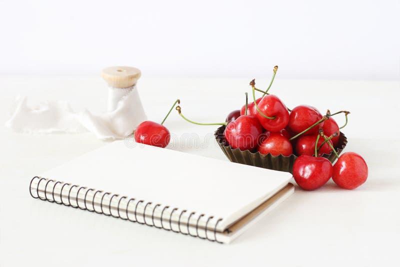 Kvinnlig stillebensammansättning Söt röd körsbärsröd frukt i liten metallbunke, tom anteckningsbok och rulle av det siden- bandet arkivbild