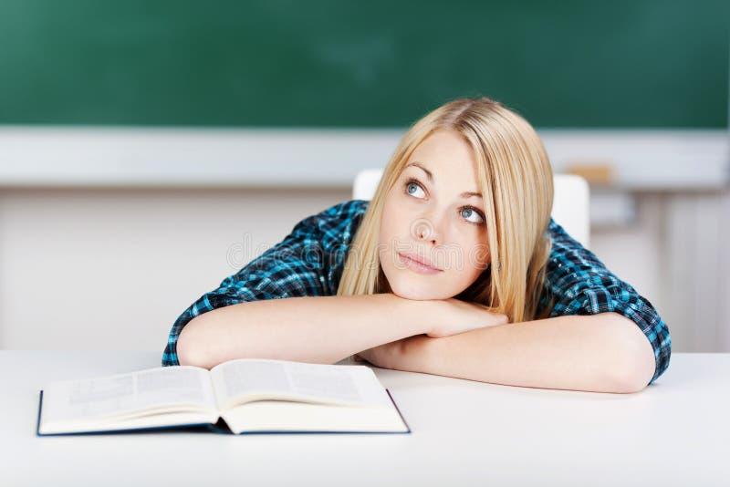 Kvinnlig student With Book Leaning på skrivbordet arkivbilder