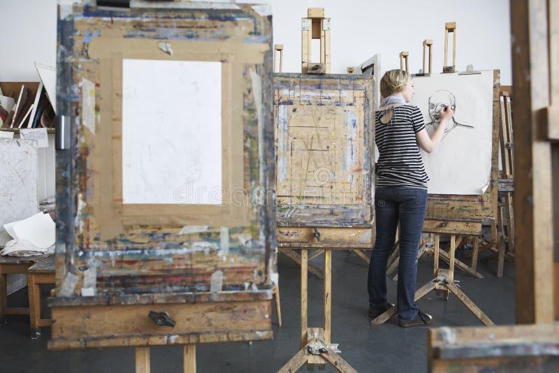 Kvinnlig student Drawing With Charcoal i Art Studio royaltyfri fotografi