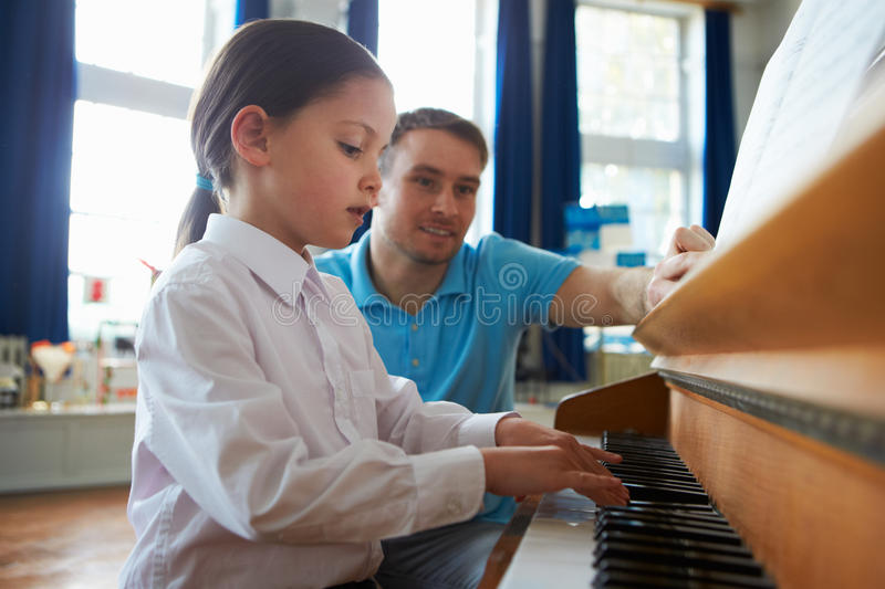Kvinnlig student Enjoying Piano Lesson med läraren arkivbild