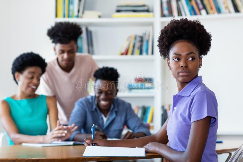 Kvinnlig student för afrikansk amerikan som lär på skrivbordet på skola royaltyfria bilder