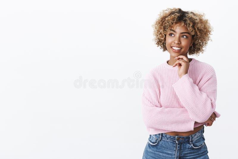 Kvinnlig student för attraktiv ung afrikansk amerikan med innehavhanden för blont hår på hakan och se förtjust på övre royaltyfria bilder
