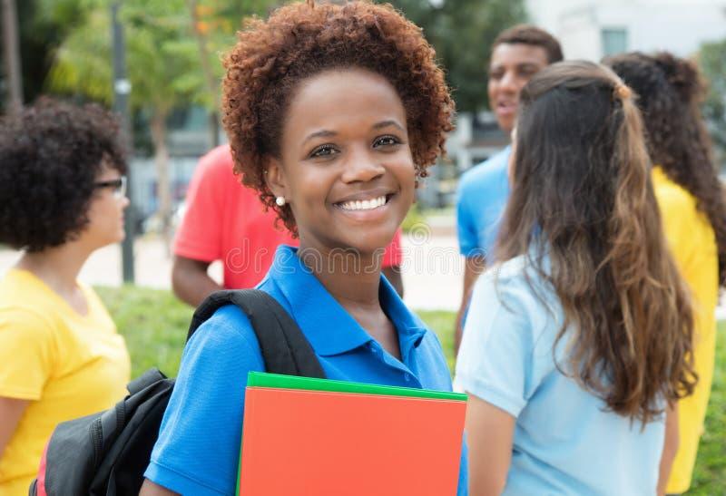 Kvinnlig student för lyckad afrikansk amerikan med den stora gruppen av I arkivbilder