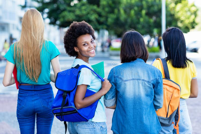 Kvinnlig student för ung afrikansk amerikan med gruppen av vänner royaltyfria foton