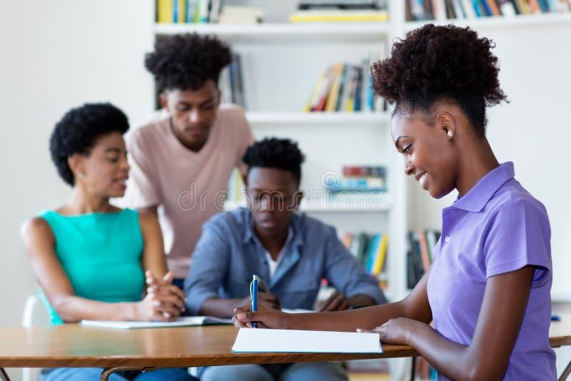 Kvinnlig student för ung afrikansk amerikan som lär på skrivbordet på skola royaltyfri foto